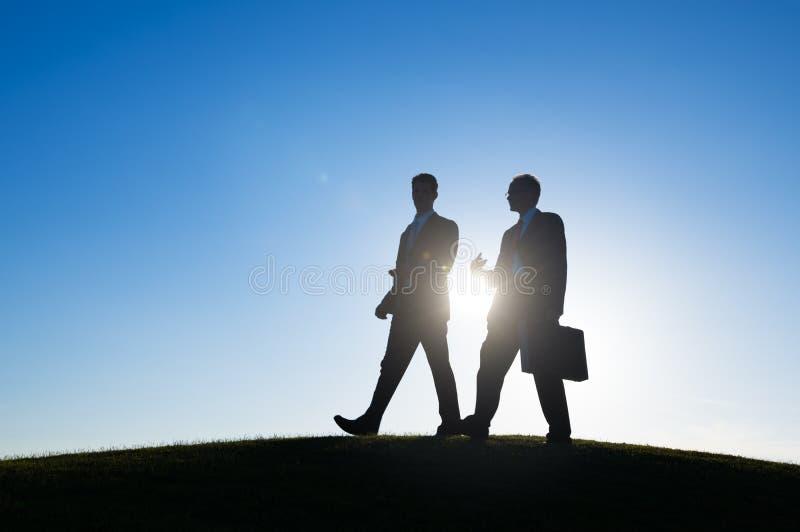 Hombre de negocios que camina junto el hablar de la conversación imagenes de archivo