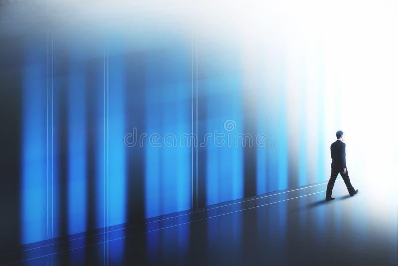 Hombre de negocios que camina a lo largo de la pared imagen de archivo