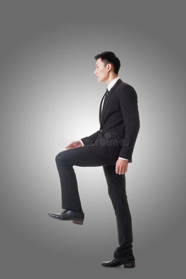 Hombre de negocios que camina para arriba en las escaleras imagen de archivo libre de regalías