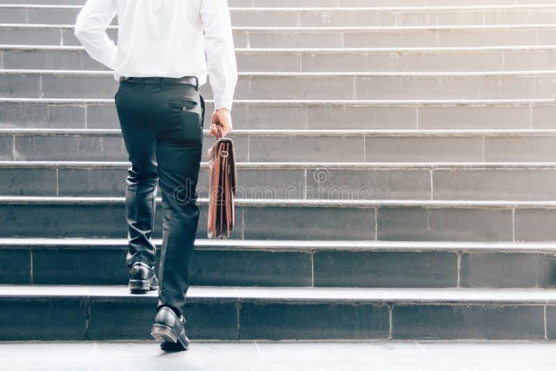 Hombre de negocios que camina para arriba en las escaleras y que sostiene la cartera fotos de archivo libres de regalías