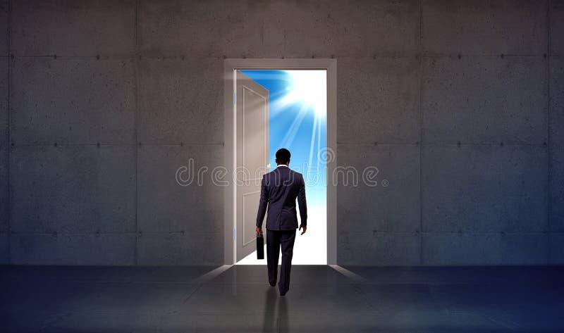 Hombre de negocios que camina a través de puerta abierta foto de archivo