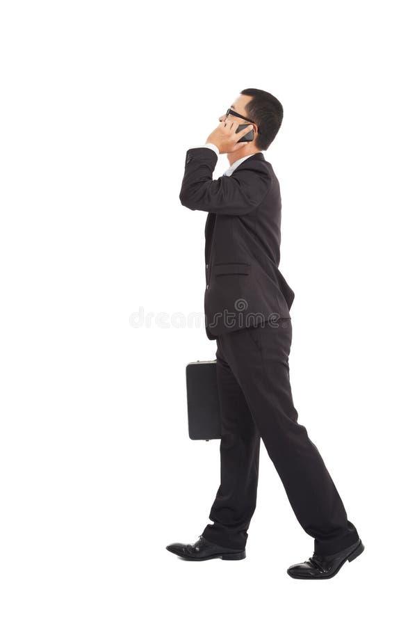 Hombre de negocios que camina y que habla en el teléfono imagen de archivo libre de regalías