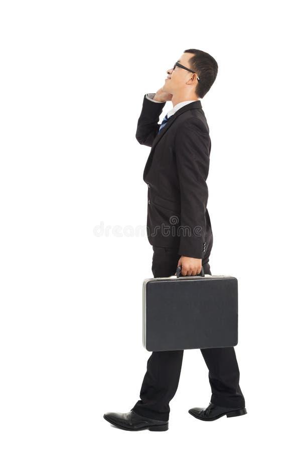 Hombre de negocios que camina y que habla en el teléfono fotos de archivo