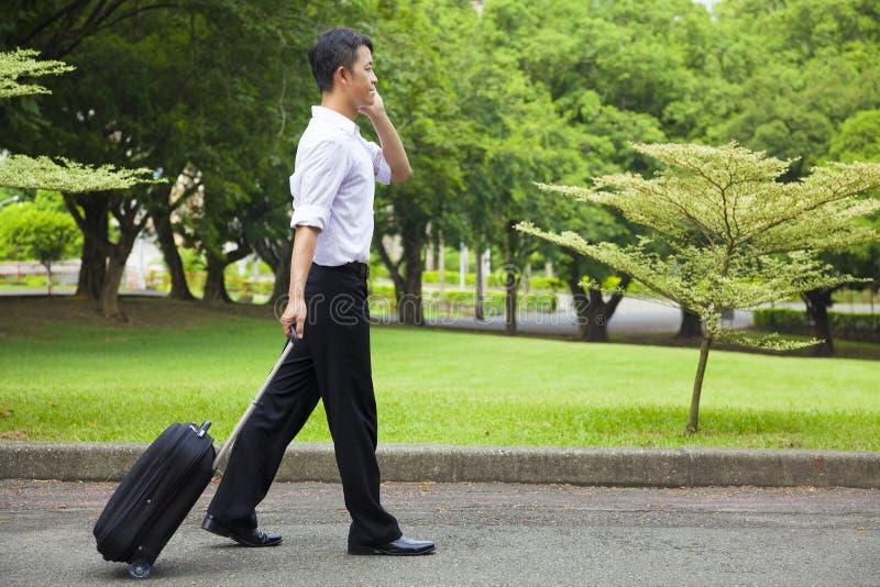 Hombre de negocios que camina y que usa un teléfono en el camino foto de archivo