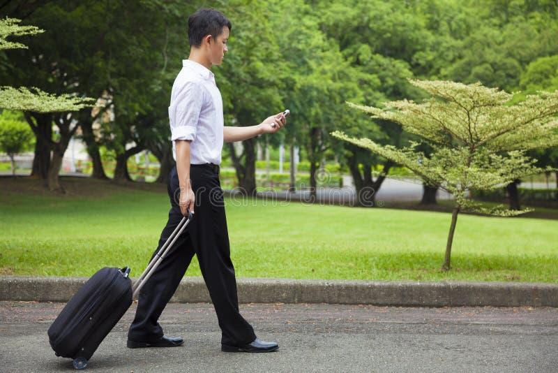 Hombre de negocios que camina y que usa un teléfono en el camino fotografía de archivo