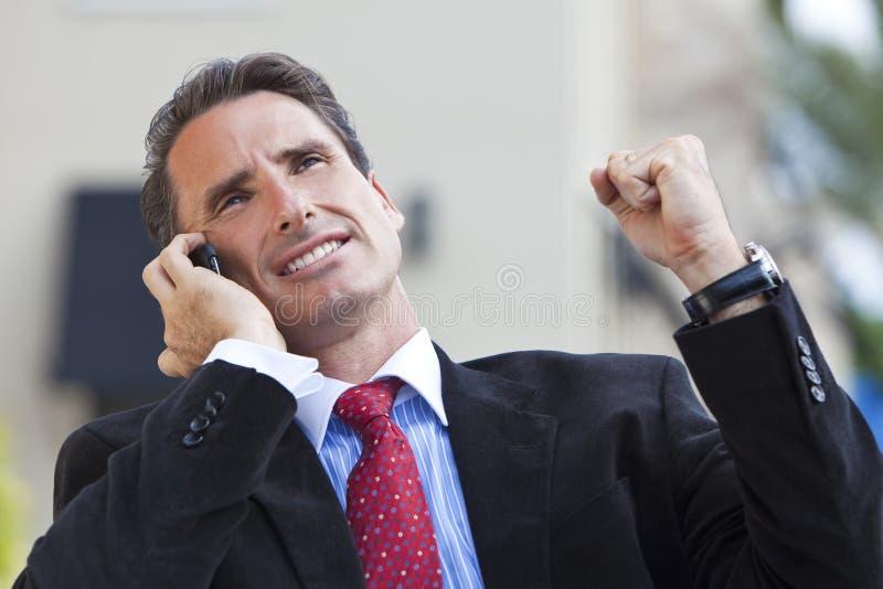 Hombre de negocios que celebra éxito en el teléfono celular fotografía de archivo libre de regalías