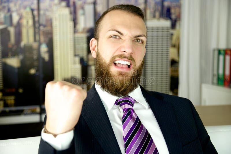 Hombre de negocios que celebra éxito en oficina foto de archivo