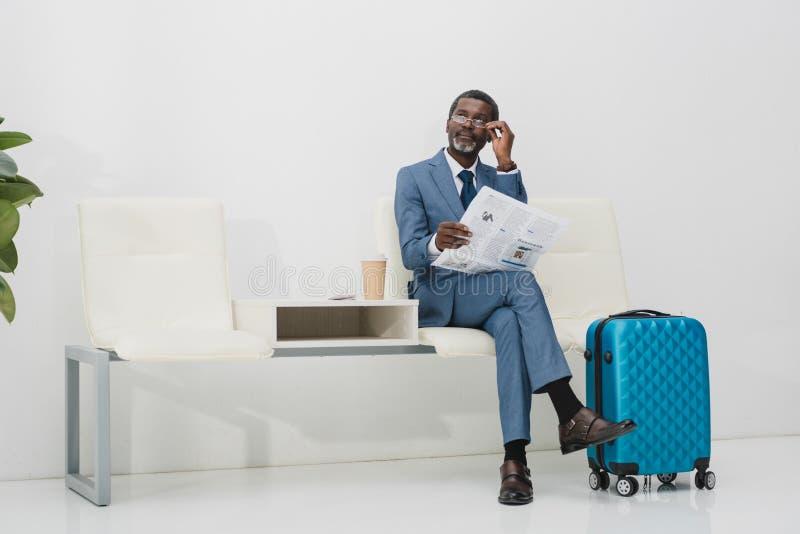Hombre de negocios que celebra el periódico y la mirada imagen de archivo