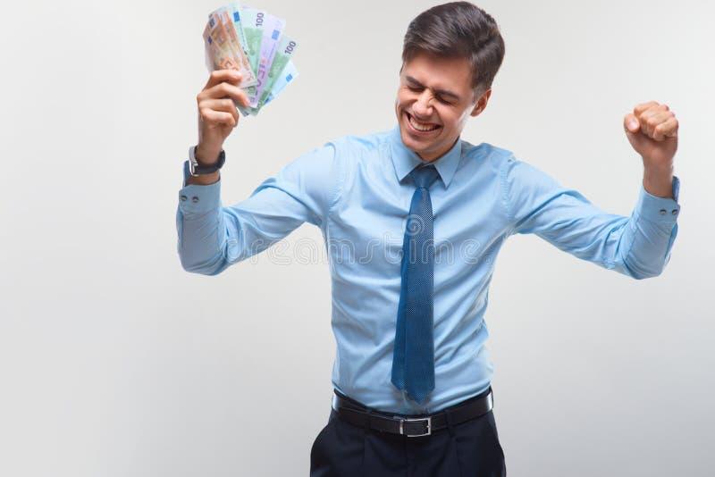 Hombre de negocios que celebra renta de dinero contra el fondo blanco fotos de archivo libres de regalías