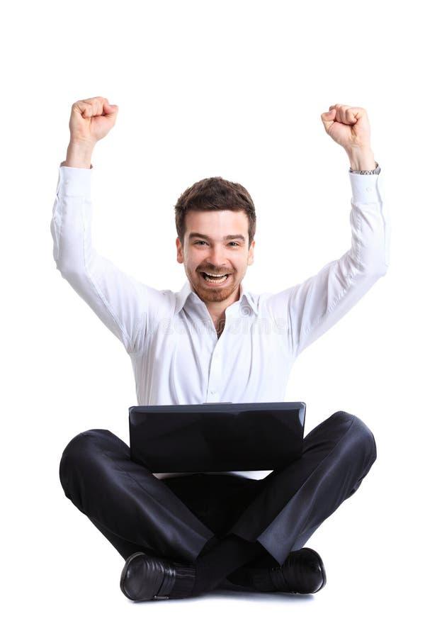 Hombre de negocios que celebra su éxito con un ordenador imagen de archivo