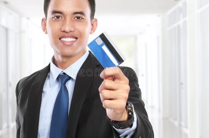 Hombre de negocios que celebra una tarjeta y una sonrisa de crédito foto de archivo