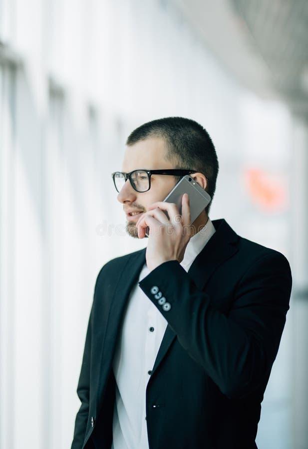 Hombre de negocios que coloca el edificio de oficinas interior y que usa el teléfono celular Sirva la ventana que hace una pausa  imagen de archivo