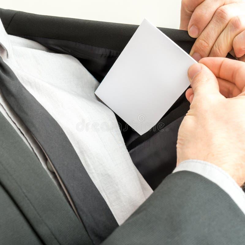 Hombre de negocios que coloca una tarjeta de visita en blanco en el bolsillo interno de fotografía de archivo