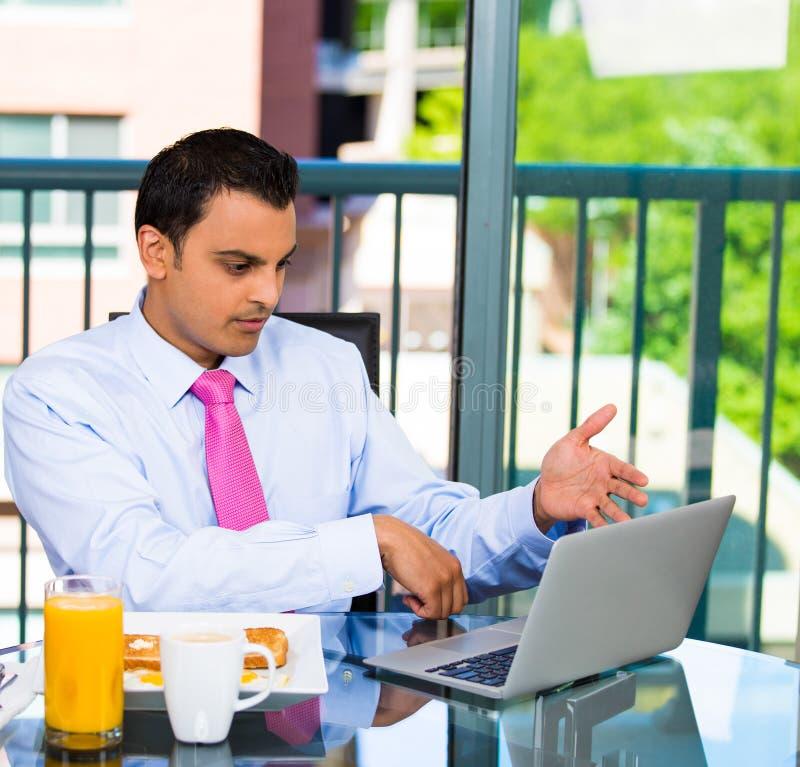 Hombre de negocios que come el desayuno y el trabajo foto de archivo libre de regalías