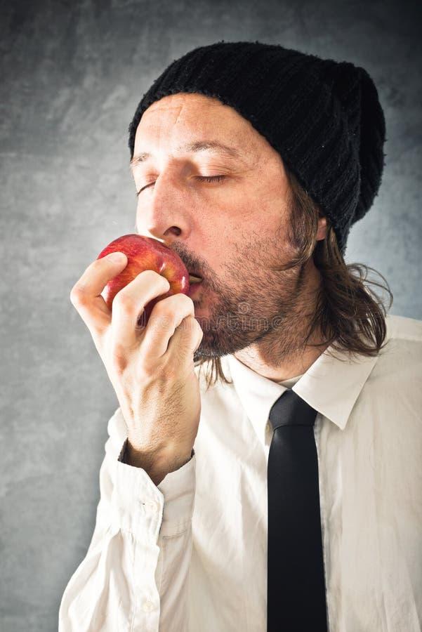 Hombre de negocios que come la manzana roja imagen de archivo