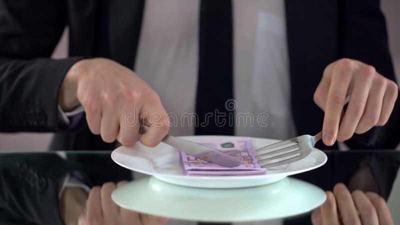 Hombre de negocios que come los billetes de banco euro, malgastando concepto, malversación del presupuesto fotografía de archivo libre de regalías