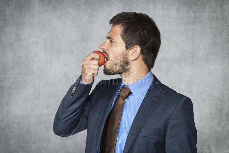 Hombre de negocios que come una manzana imágenes de archivo libres de regalías