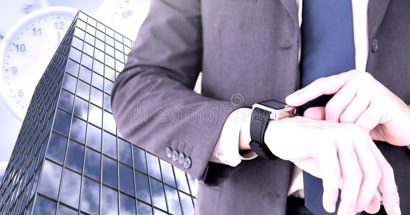Hombre de negocios que comprueba el reloj del tiempo y el edificio alto con los relojes foto de archivo