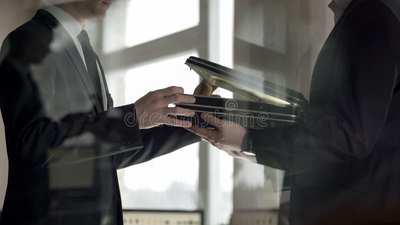 Hombre de negocios que comprueba los d?lares en cartera, contragolpe en la cooperaci?n ilegal foto de archivo libre de regalías