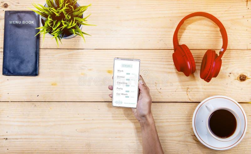 Hombre de negocios que comprueba su horario en smartphone en el café fotografía de archivo