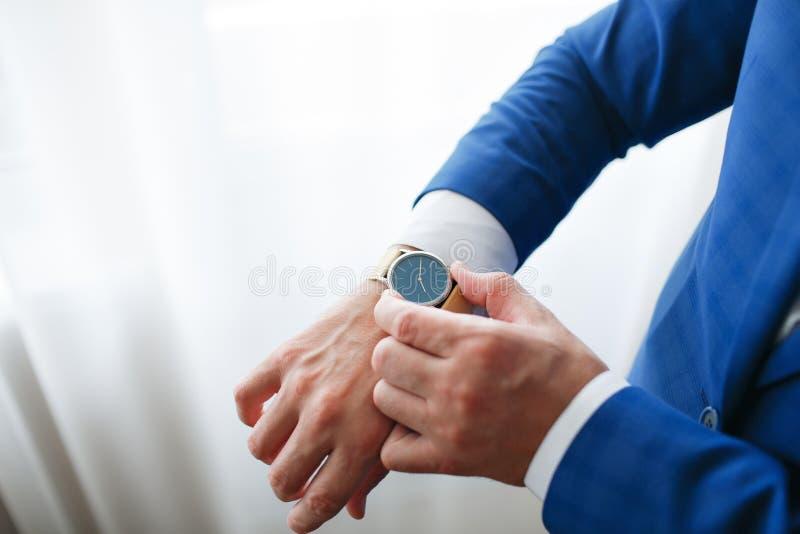 Hombre de negocios que comprueba tiempo en su reloj mano del ` s de los hombres con un reloj imagen de archivo