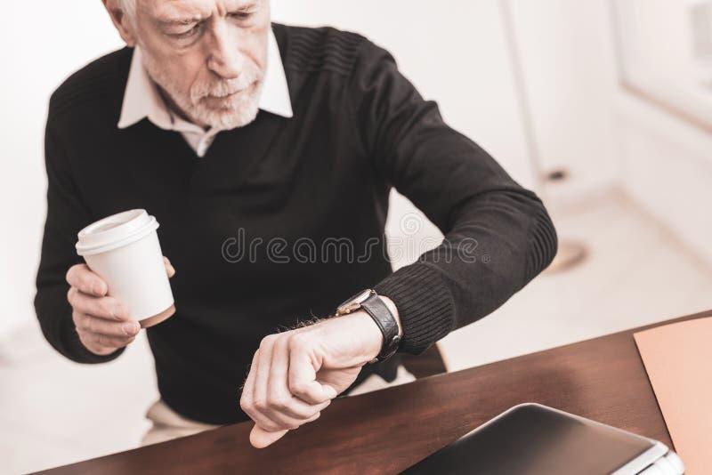 Hombre de negocios que comprueba tiempo en su reloj imagen de archivo