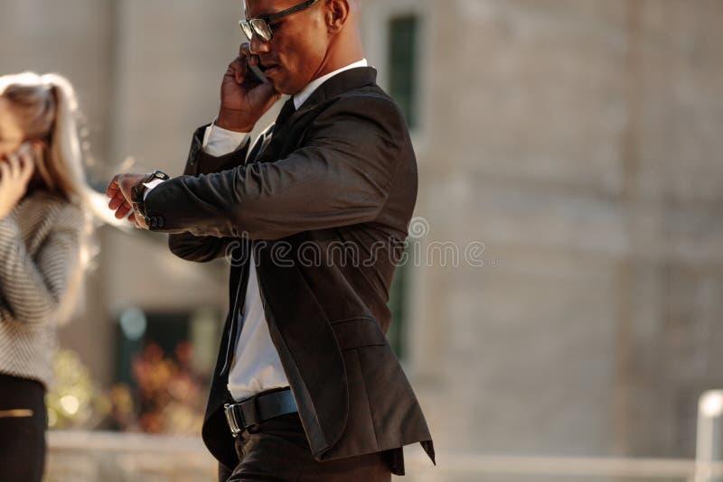 Hombre de negocios que comprueba tiempo mientras que va a la oficina foto de archivo