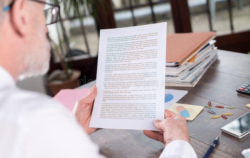 Hombre de negocios que comprueba un documento fotografía de archivo libre de regalías