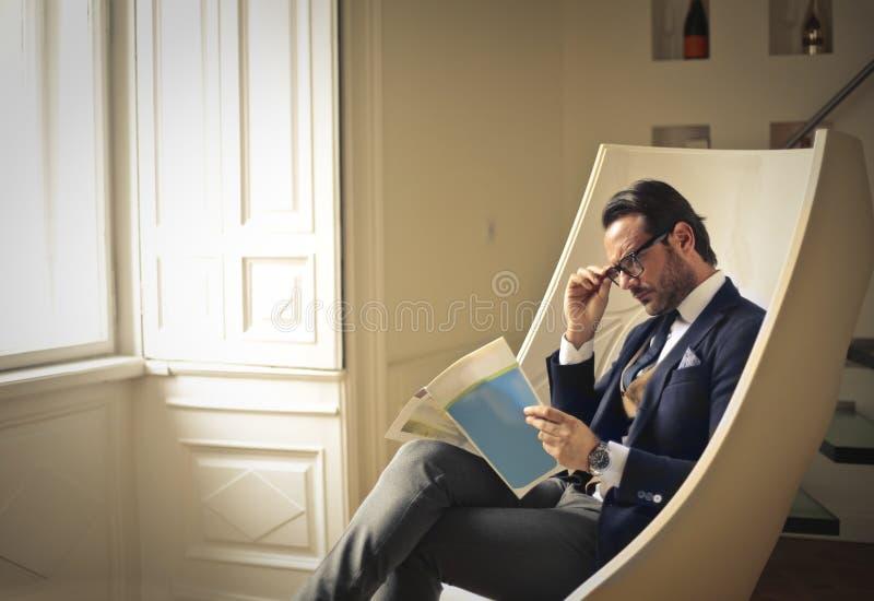 Hombre de negocios que comprueba una revista fotos de archivo libres de regalías