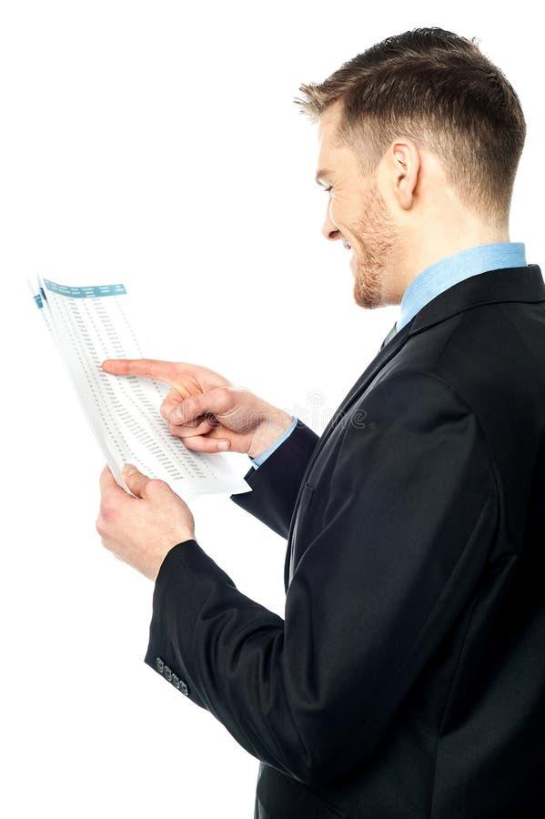 Hombre de negocios que comprueba varias veces informes anuales foto de archivo libre de regalías