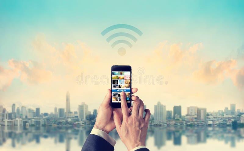 Hombre de negocios que conecta pagos móviles con la red de Wifi en el ci fotos de archivo libres de regalías