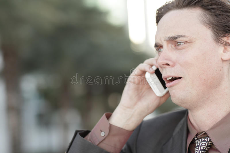 Hombre de negocios que consigue encendido sobre el teléfono foto de archivo