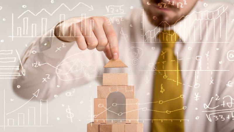 Hombre de negocios que construye una torre imagenes de archivo