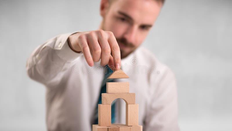Hombre de negocios que construye una torre imagen de archivo