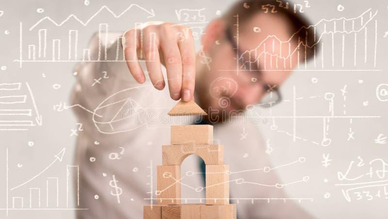 Hombre de negocios que construye una torre foto de archivo libre de regalías