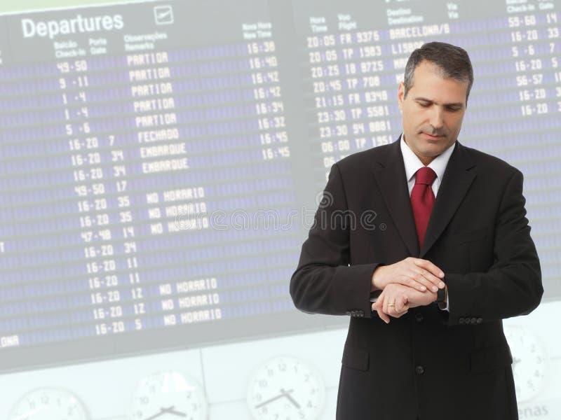 Hombre de negocios que controla tiempo en su reloj imágenes de archivo libres de regalías