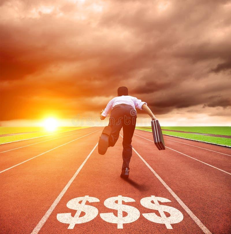 Hombre de negocios que corre en pista con la muestra del dinero imagenes de archivo