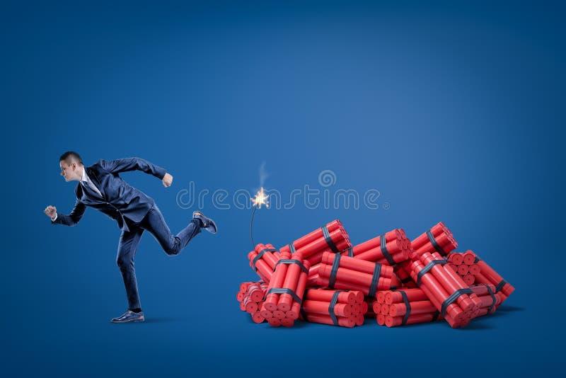 Hombre de negocios que corre lejos del paquete de palillos rojos de la dinamita del tnt con el fusible encendido en fondo azul ilustración del vector