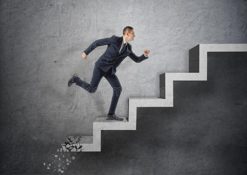 Hombre de negocios que corre para arriba la escalera concreta, que está machacando abajo después de él fotografía de archivo libre de regalías