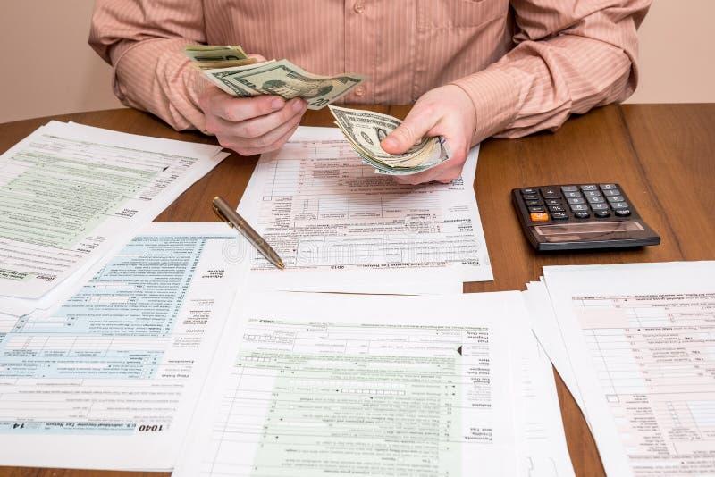 Hombre de negocios que cuenta dólares con las formas de impuesto fotografía de archivo libre de regalías