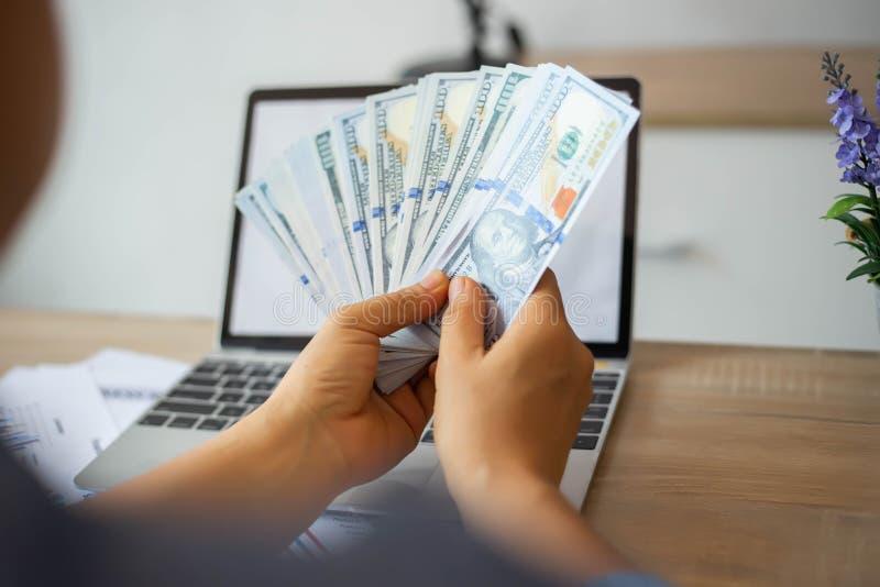 Hombre de negocios que cuenta el billete de banco del dólar foto de archivo