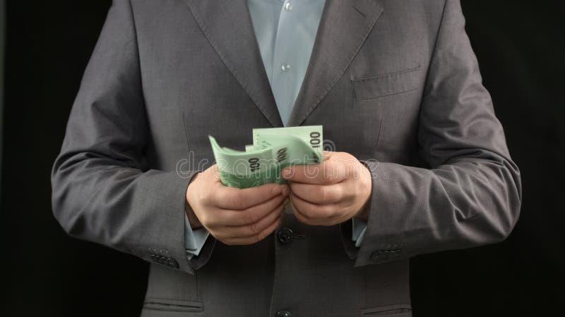 Hombre de negocios que cuenta el dinero, la buena renta o los ahorros, concepto de la estrategia del éxito foto de archivo libre de regalías
