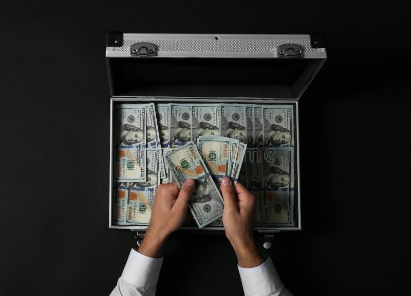 Hombre de negocios que cuenta el dinero sobre la maleta en fondo oscuro foto de archivo