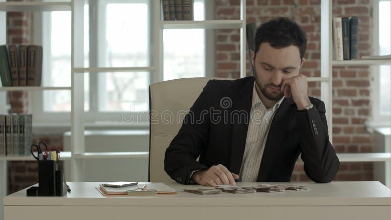 Hombre de negocios que cuenta hacia fuera algunos billetes de banco fotografía de archivo