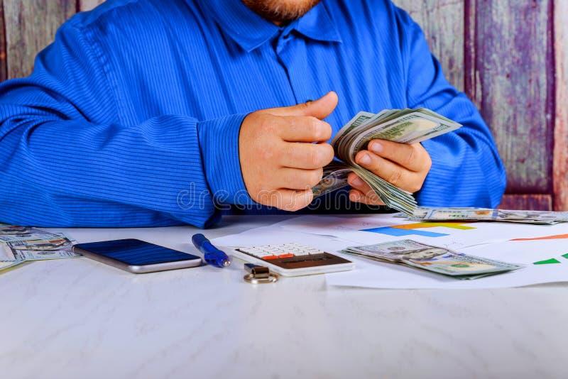 Hombre de negocios que cuenta U S funcionamiento que considera de los billetes de dólar imagenes de archivo