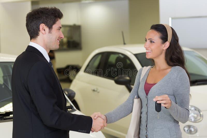 Hombre de negocios que da llave del coche mientras que sacude una mano del cliente fotos de archivo libres de regalías