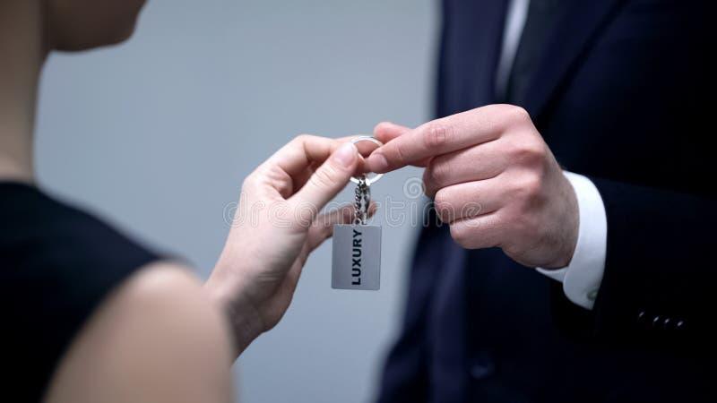 Hombre de negocios que da llaves de la señora al alojamiento de lujo, centro turístico superior de la calidad fotos de archivo libres de regalías