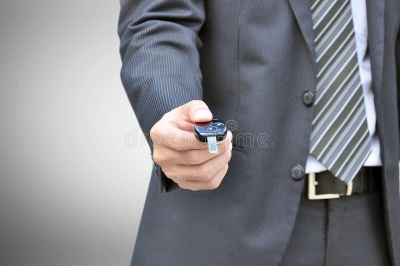 Hombre de negocios que da una llave del coche - venta del coche y concepto del negocio del alquiler imagenes de archivo