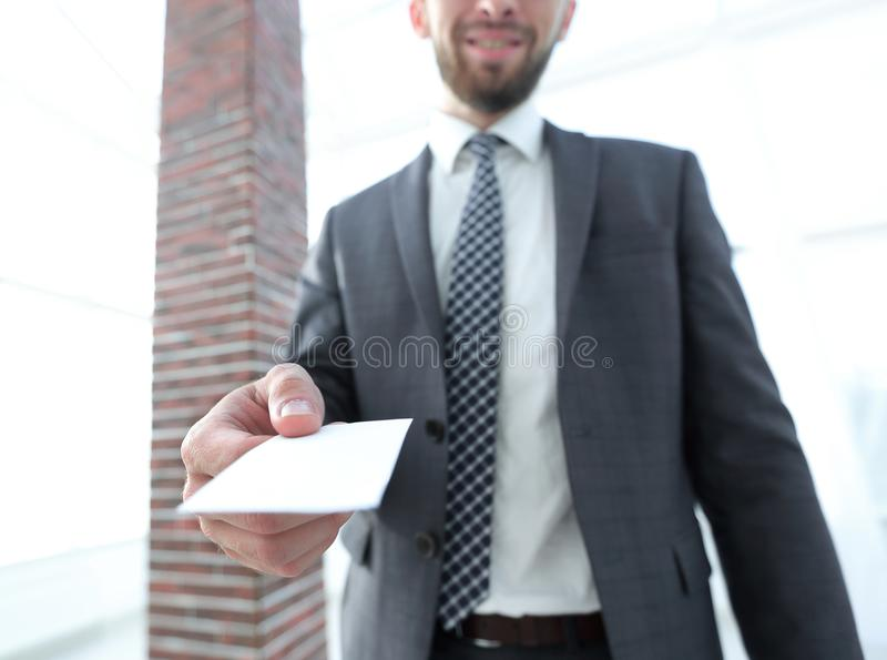 Hombre de negocios que da una tarjeta Foto del primer en oficina del desván fotografía de archivo libre de regalías