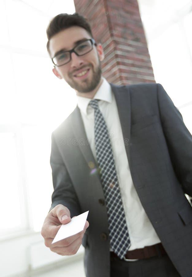 Hombre de negocios que da una tarjeta Foto del primer en oficina del desván imagen de archivo libre de regalías